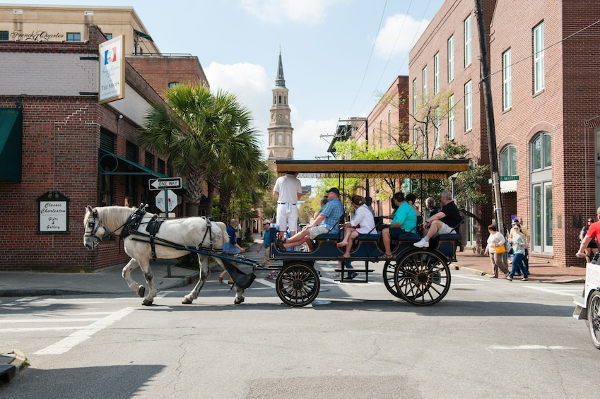Show item 1 of 8. Horse drawn carriage traveling down street in Charleston