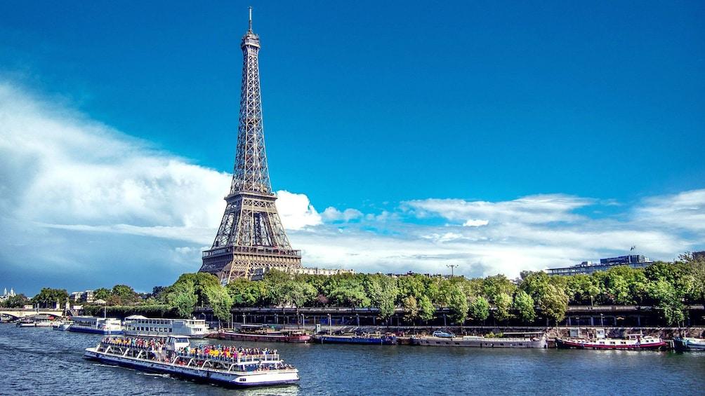 Charger l'élément 3 sur 10. Seine river cruise boat sails past Eiffel Tower in Paris