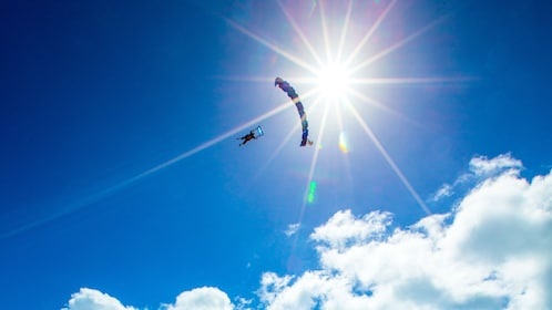 Skydiver eclipses the sun on a cloudy day