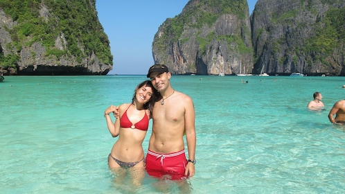 Couple wading in clear water off the coast of Koh Phi Phi