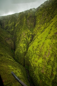 Helicopter flying over a jungle canyon in Hawaii