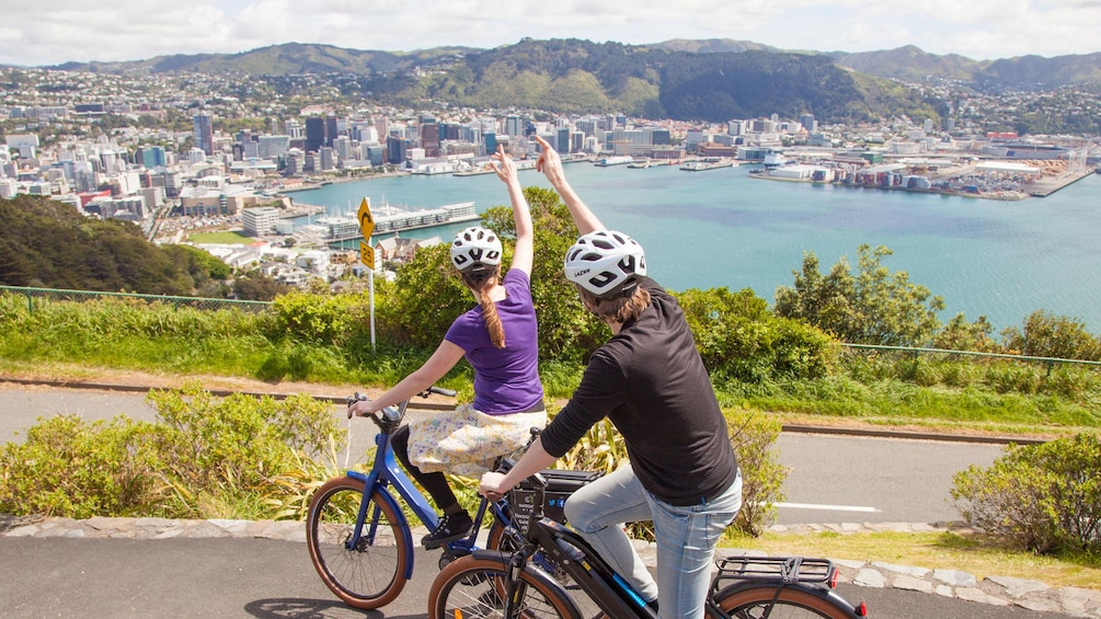 Show item 3 of 5. Couple waving on bicycles in Wellington
