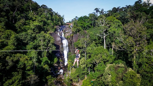 Man ziplines past waterfall in Malaysia