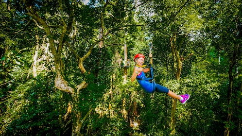 Woman gives thumbs up while ziplining in Malaysia