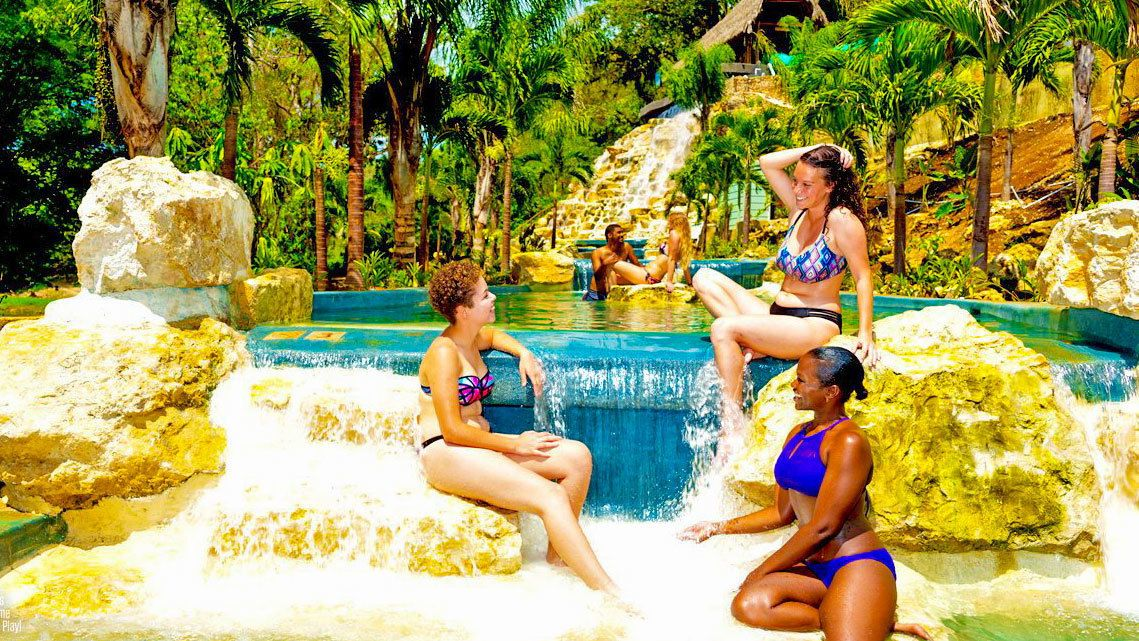 Three women next to a pool at a plantation in Jamaica