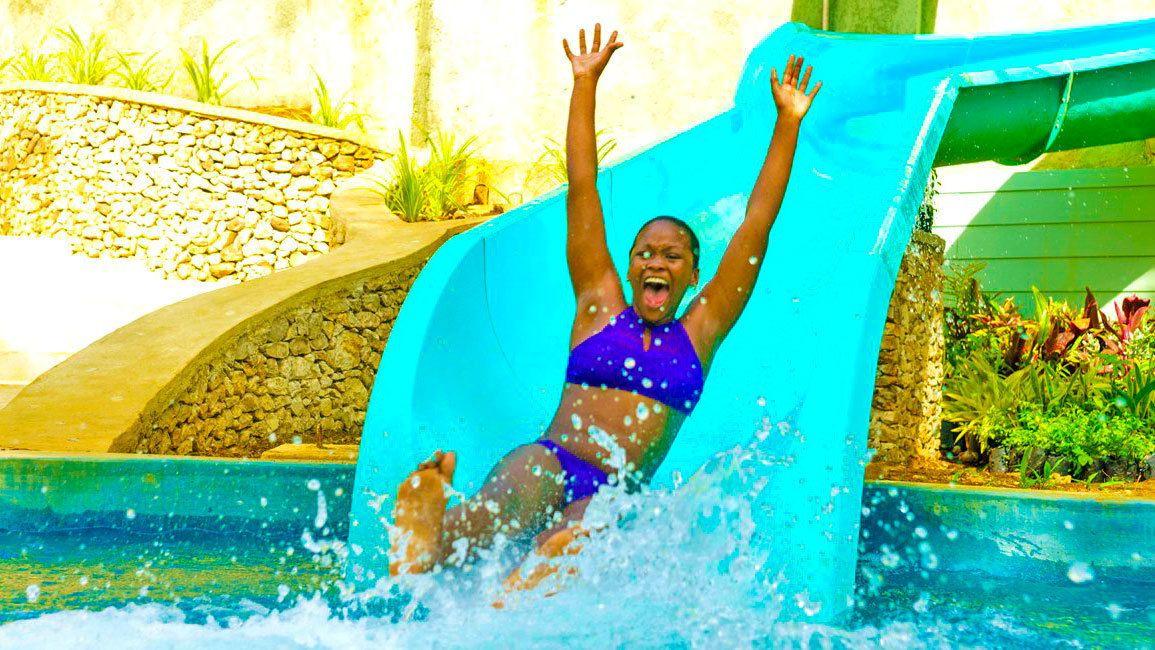 Woman slides down a slide into a pool
