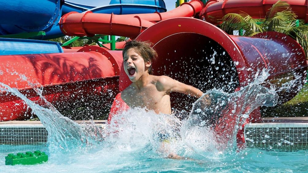 Show item 3 of 10. Boy splashing into a pool from a waterslide at Legoland in Dubai