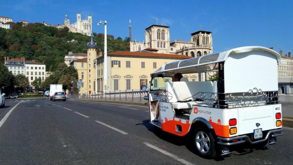 Show item 6 of 6. Tuk tuk driving down street in Lyon