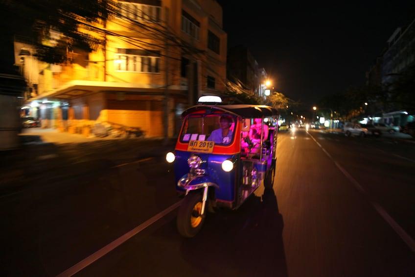 Show item 2 of 5. Tuk tuk vehicle at night in Bangkok