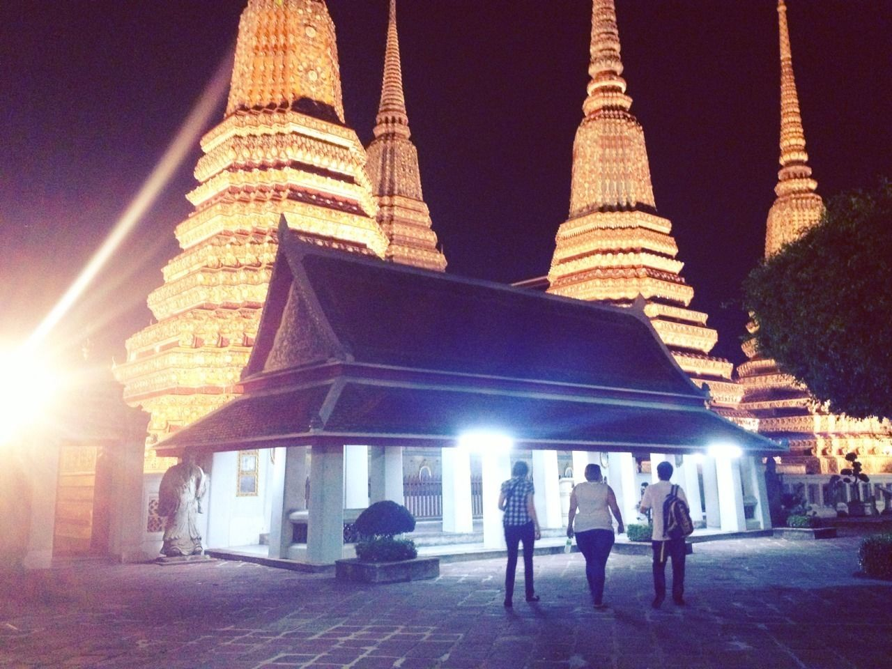 Tour group at a temple lit up at night in Bangkok