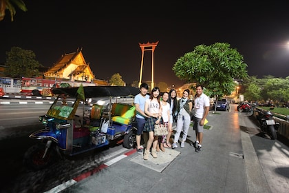Tour group with tuk tuk vehicle at night in Bangkok