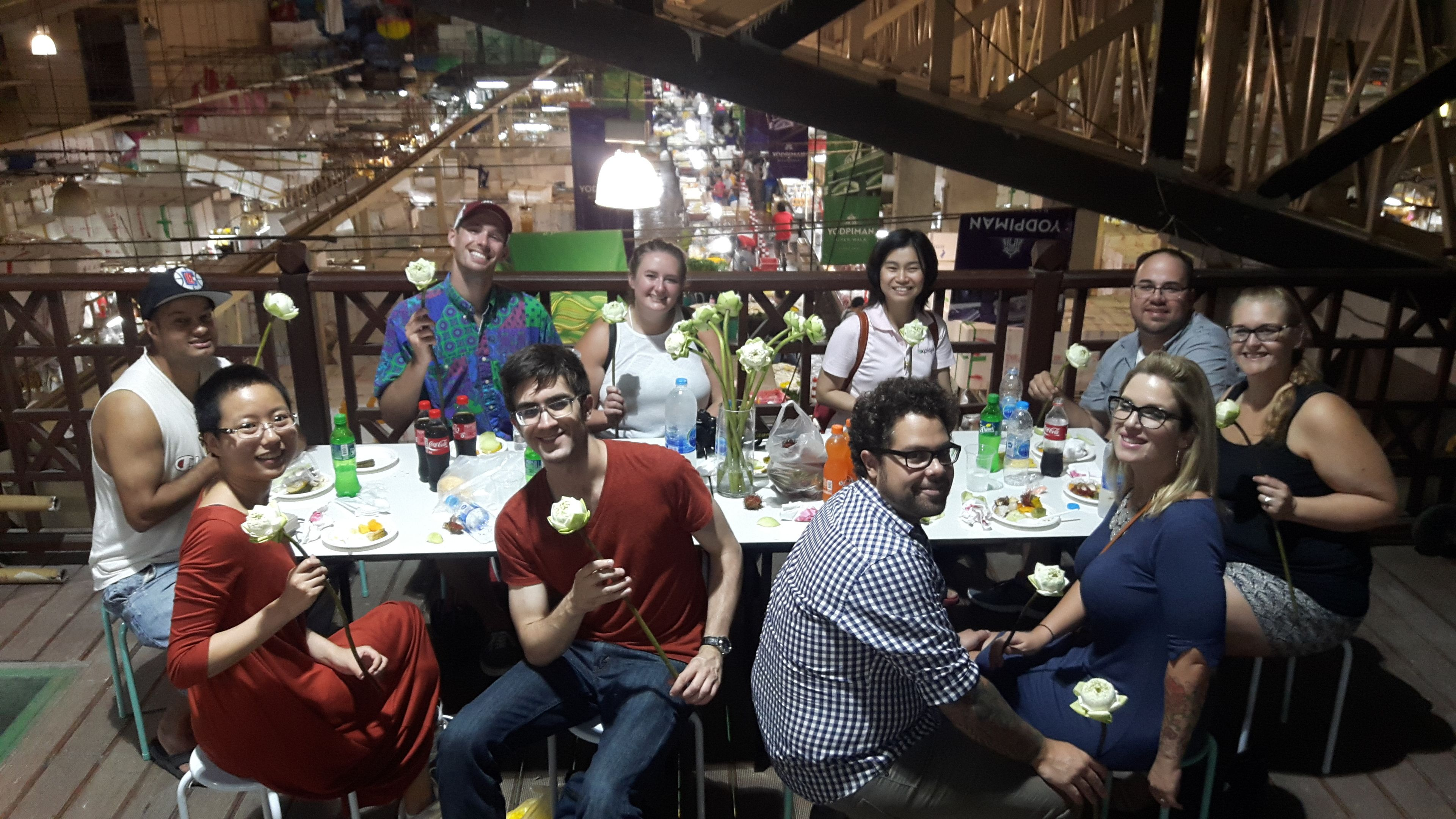 Tour group at a table holding white roses in Bangkok