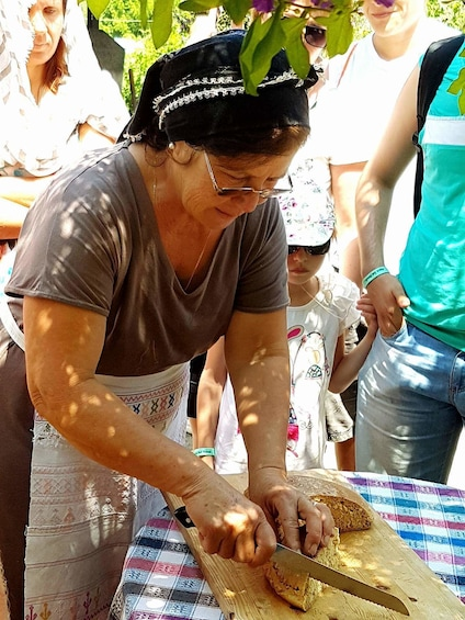 Woman slicing bread on a table outdoors in Cyprus