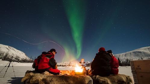 Adventurers sit around fire as Aurora Borealis streaks above in Tromso