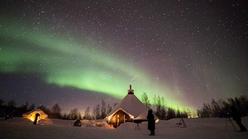 Adventurers standing outside of huts to see Aurora Borealis in Tromso