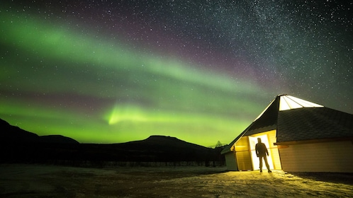 Man stands at entrance of hut with Aurora Borealis overhead in Tromso