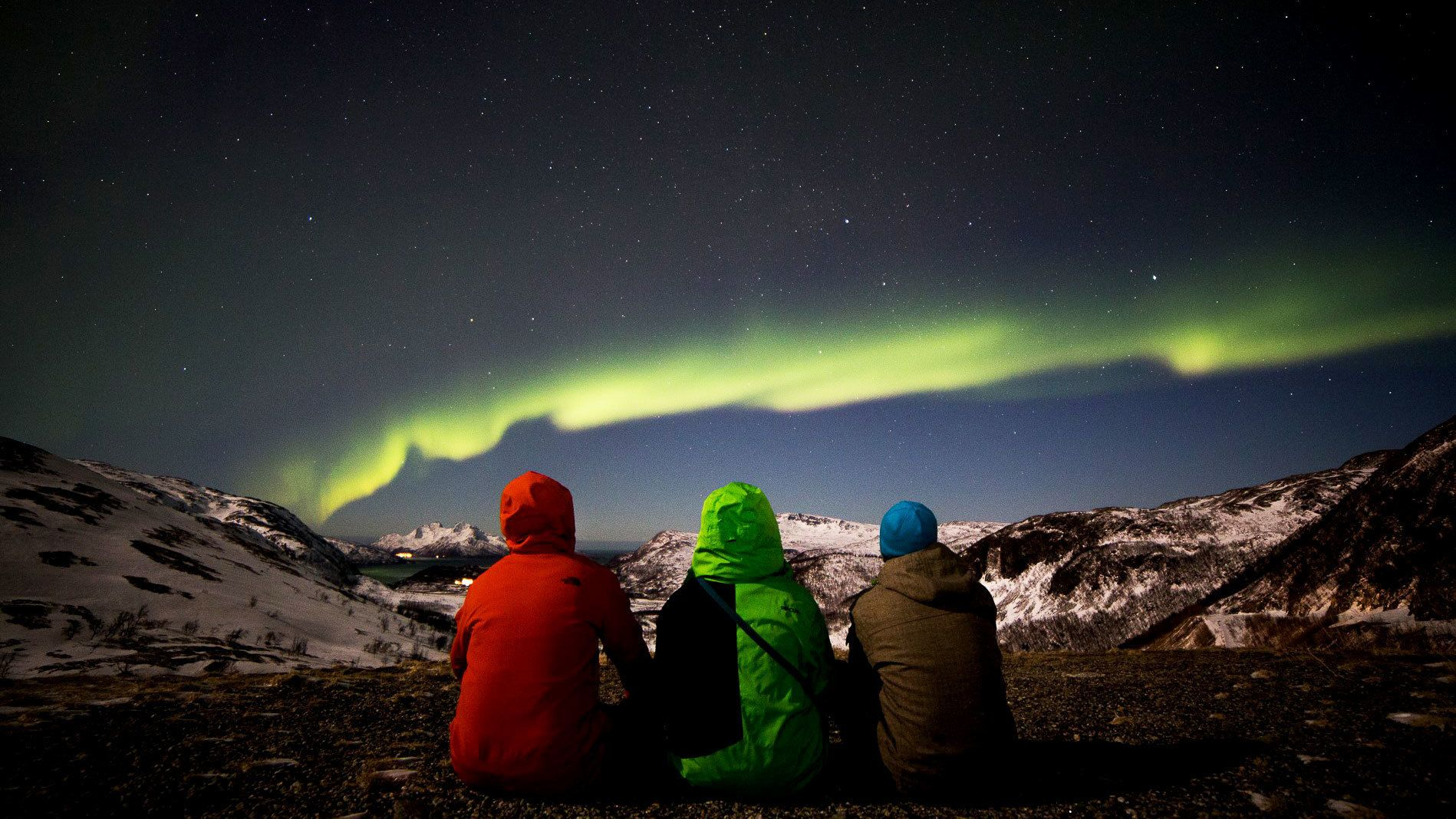 Trio sits watching aurora borealis in Tromso
