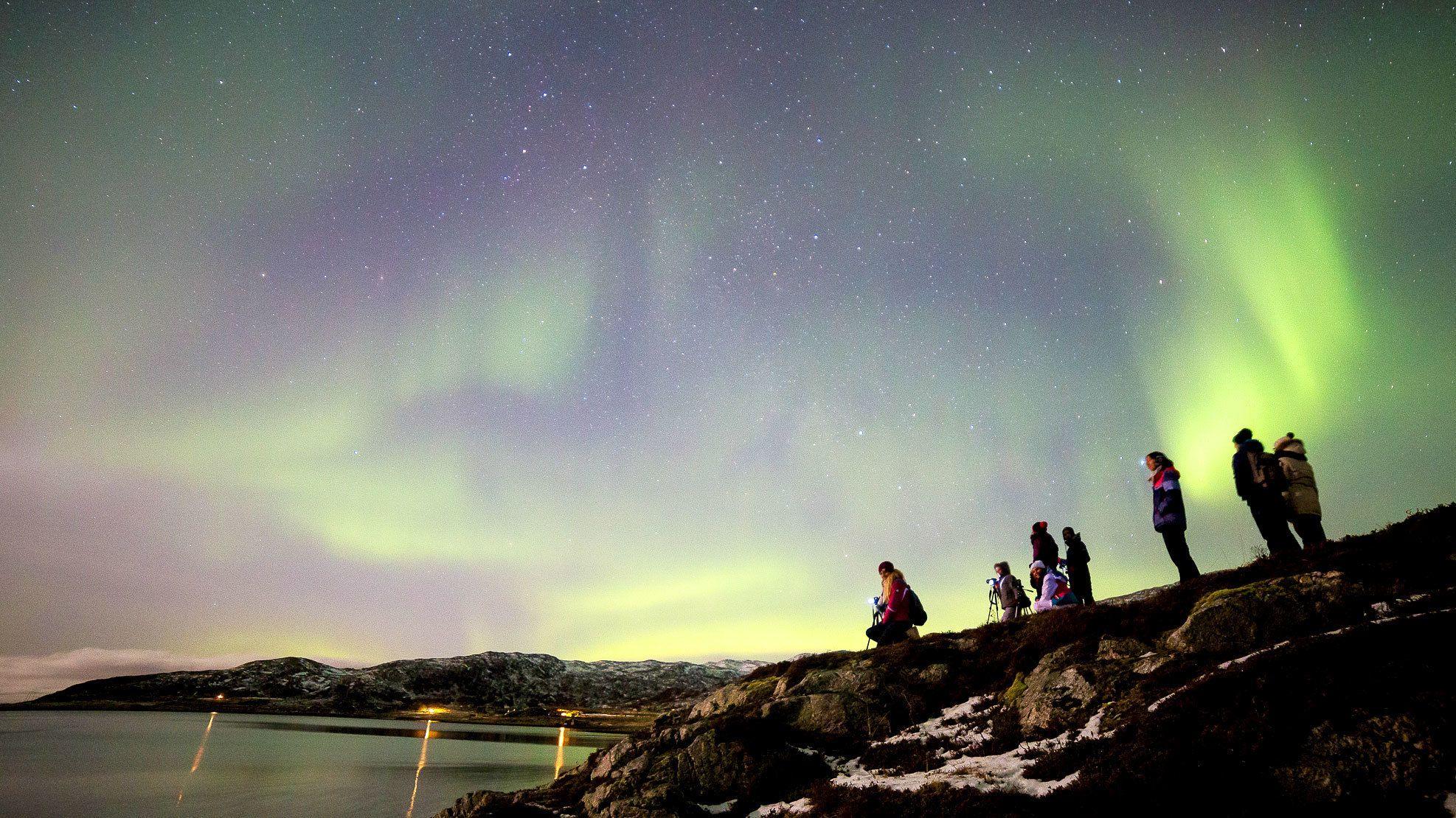 People standing upon ridge to view aurora borealis in Tromso