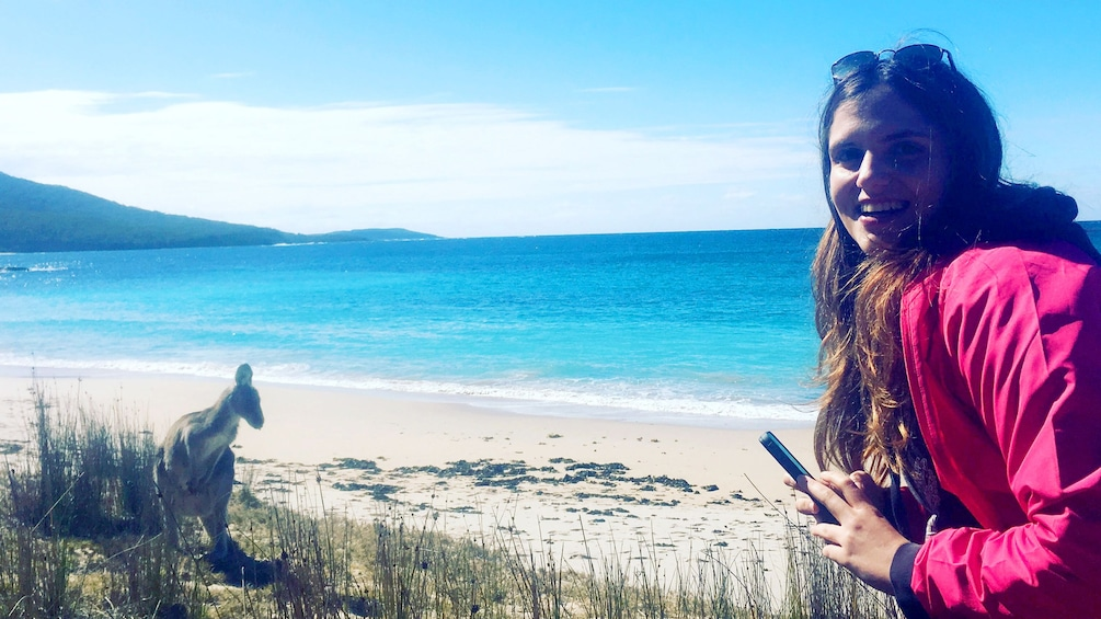 Show item 5 of 5. Woman poses next to a Kangaroo on the beach of Canberra