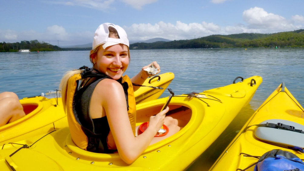 Show item 2 of 5. Woman eats a oyster in a Kayak