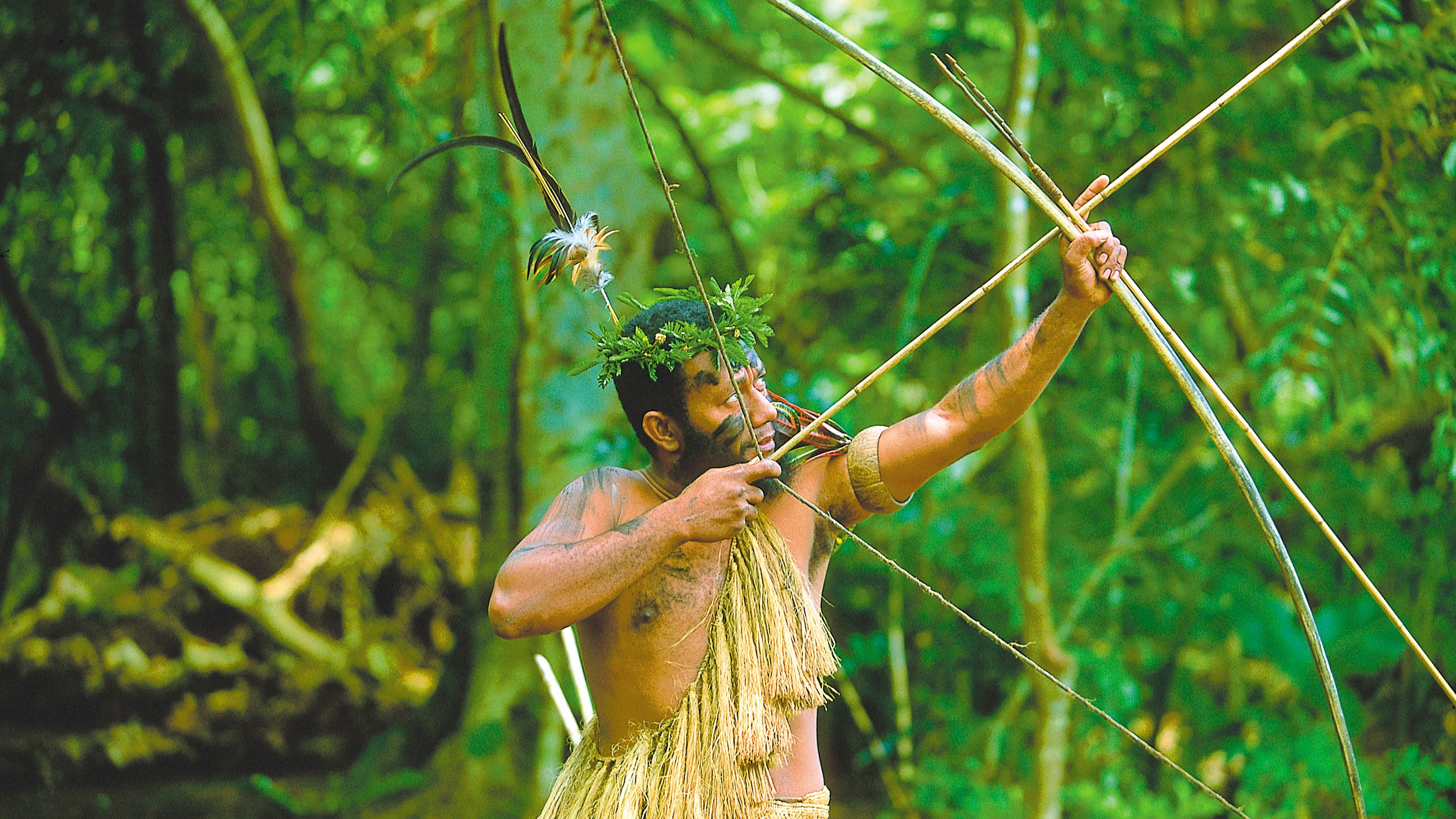 Men dressed in indigenous clothing to Vanuatu Island and holding a bow and arrow