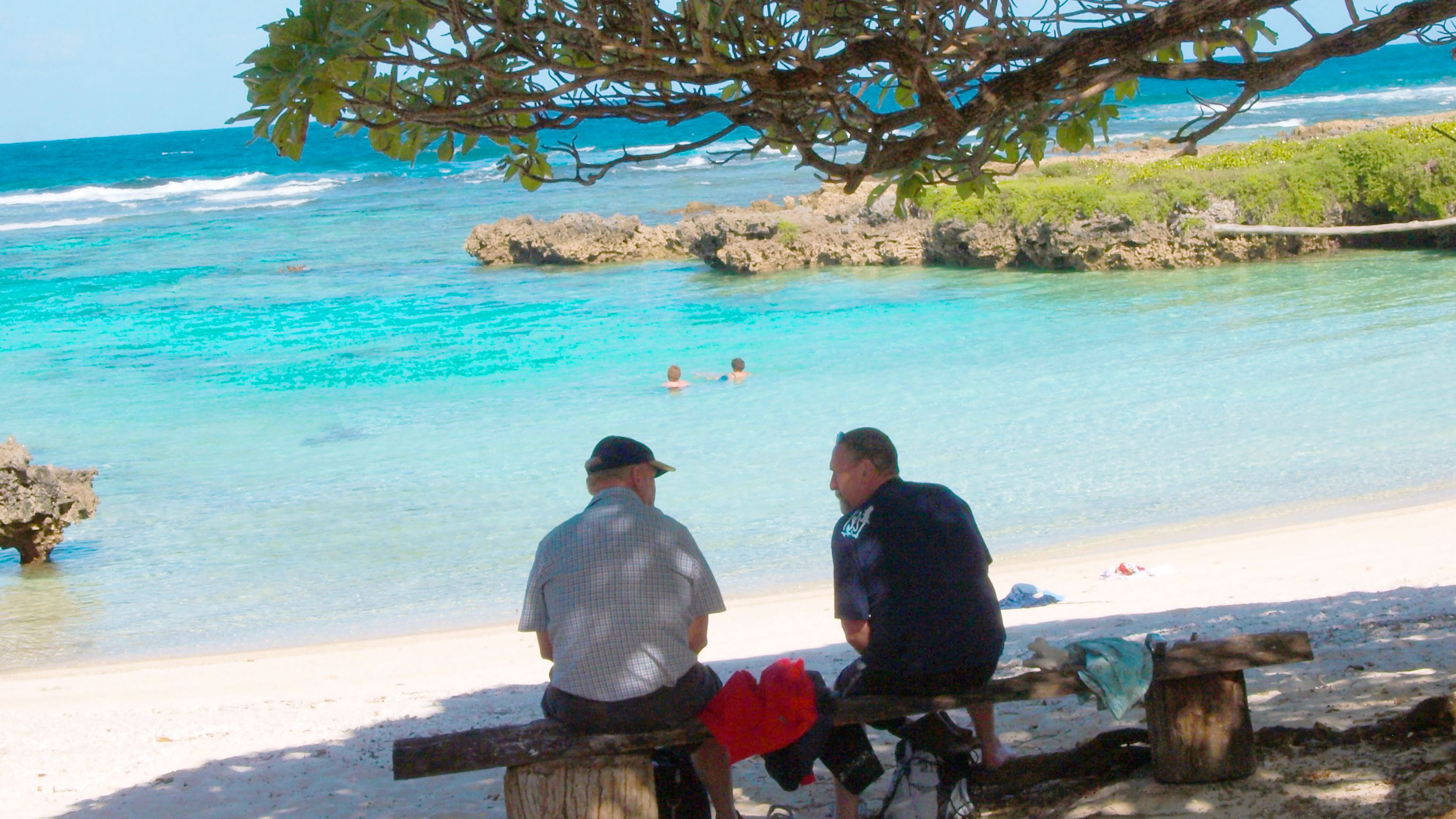 Two men sitting on a beach on Vanuatu Island