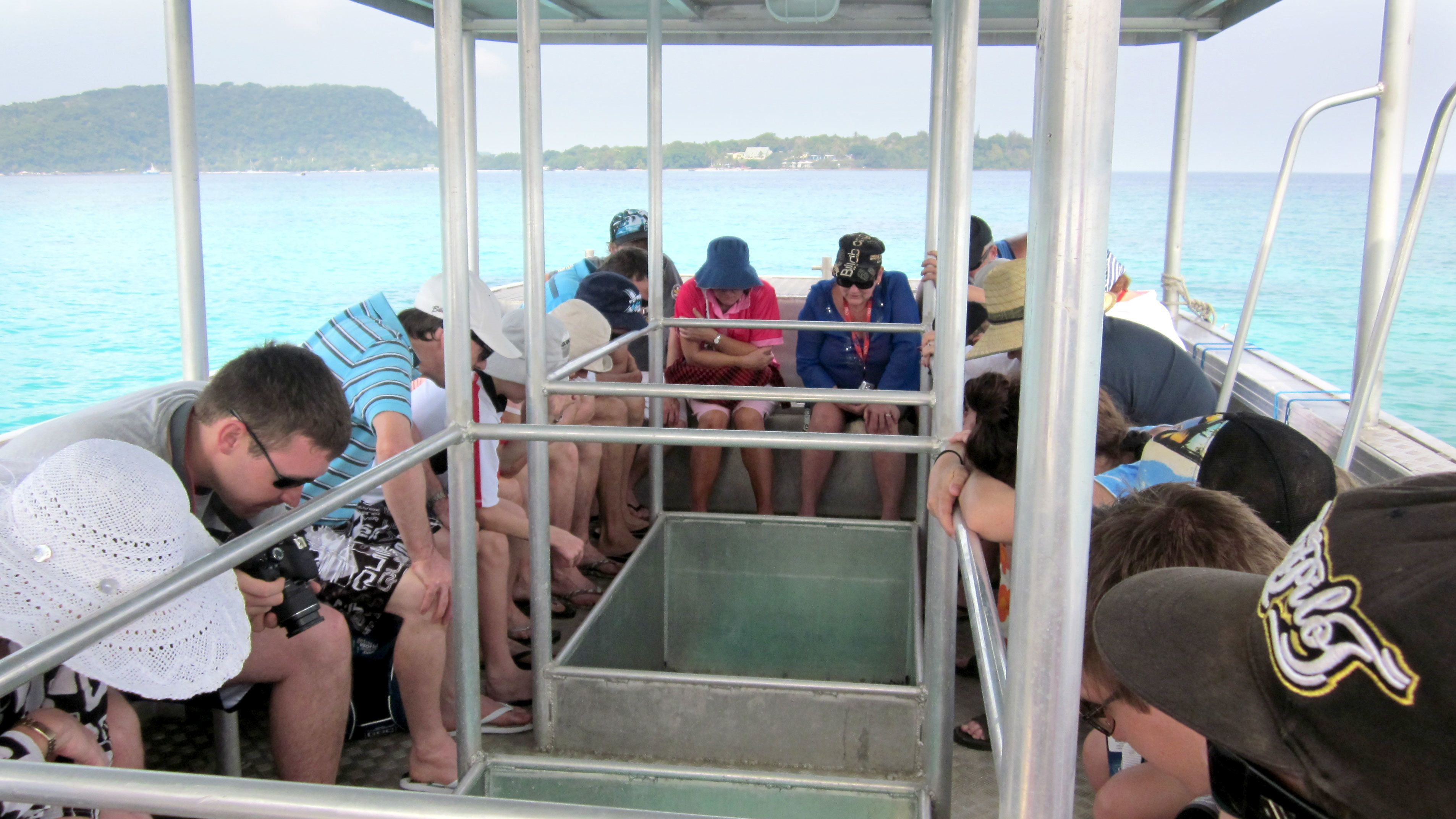 Group looking through the floor of a glass bottom boat on Vanuatu Island