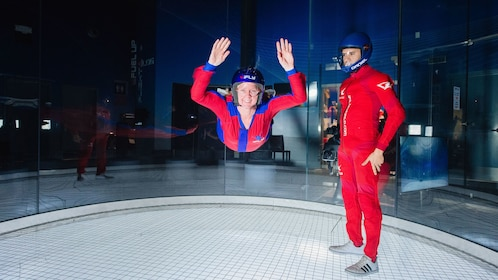 Woman flying next to instructor in iFly