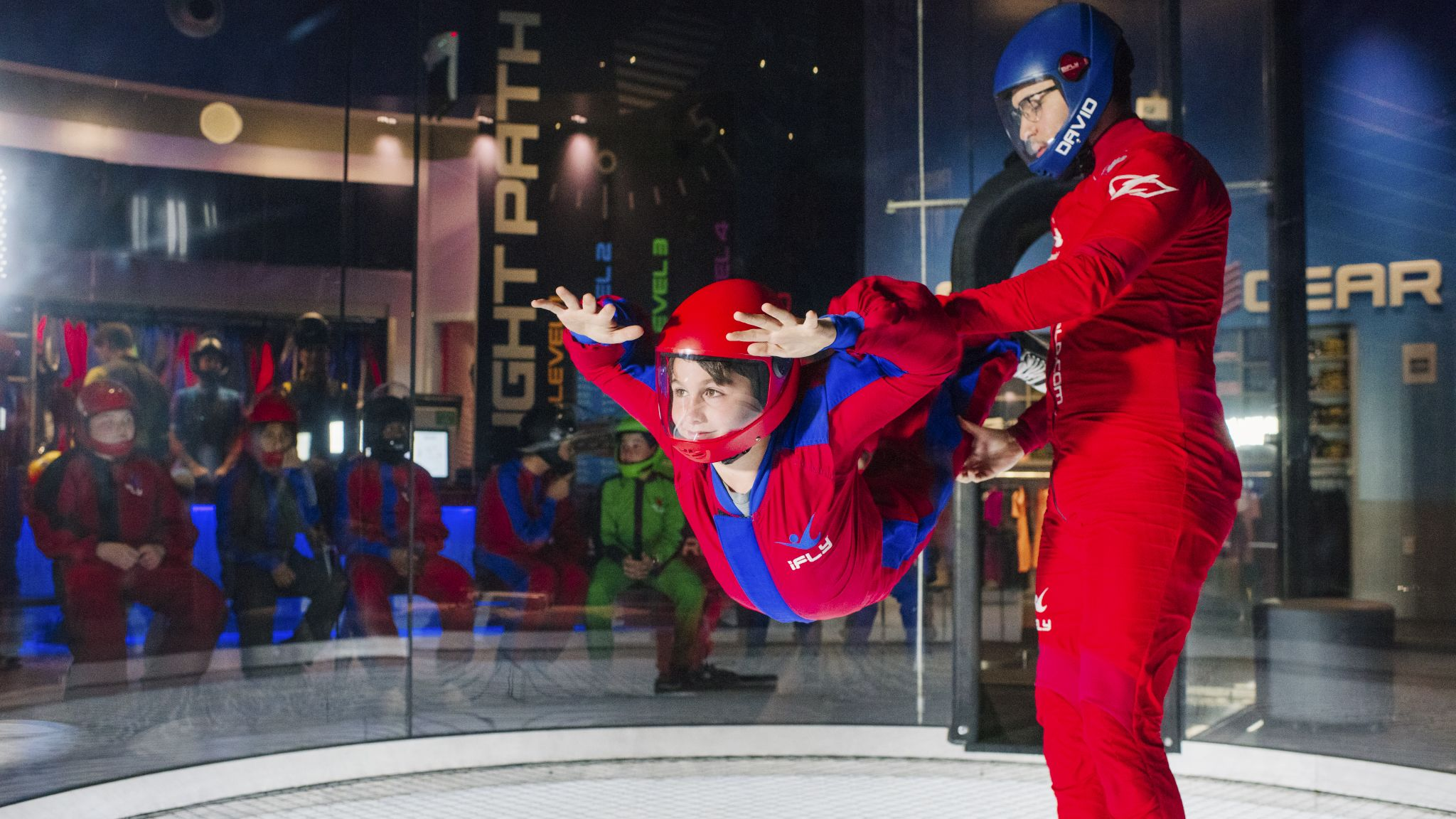 Woman flys next to an instructor in an iFly tunnel