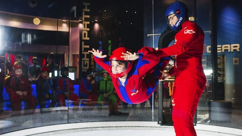 Boy with instructor in skydiving chamber at iFly