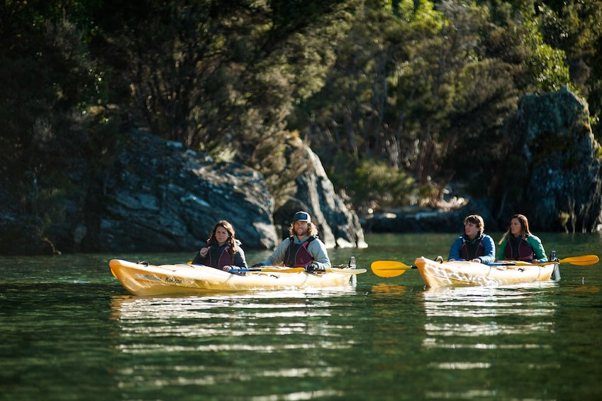Show item 3 of 4. Kayakers on still waters of Lake Wanaka in New Zealand