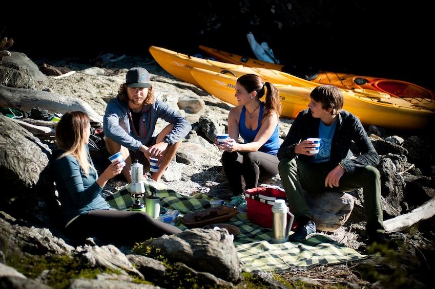 Show item 2 of 4. Kayaking group taking break on rocks of Lake Wanaka in New Zealand