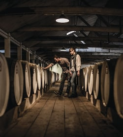 Couple looking at wine barrels in cellar in Adelaide