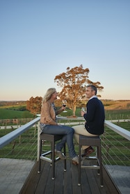 Man and woman sit on a back deck of a vineyard