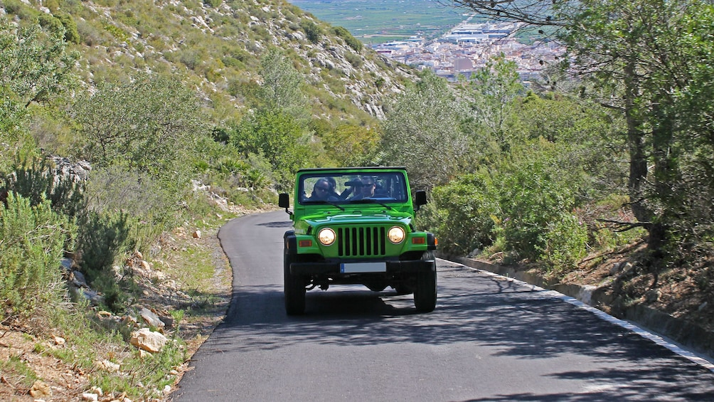 Show item 3 of 5. Green jeep driving down a road in Costa Blanca