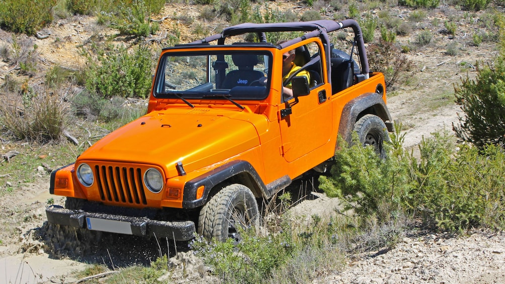 Show item 1 of 5. Orange jeep driving down a road in Costa Blanca