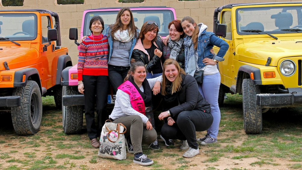 Show item 1 of 5. A group of people posing infront of colorful jeeps in Costa Blanca