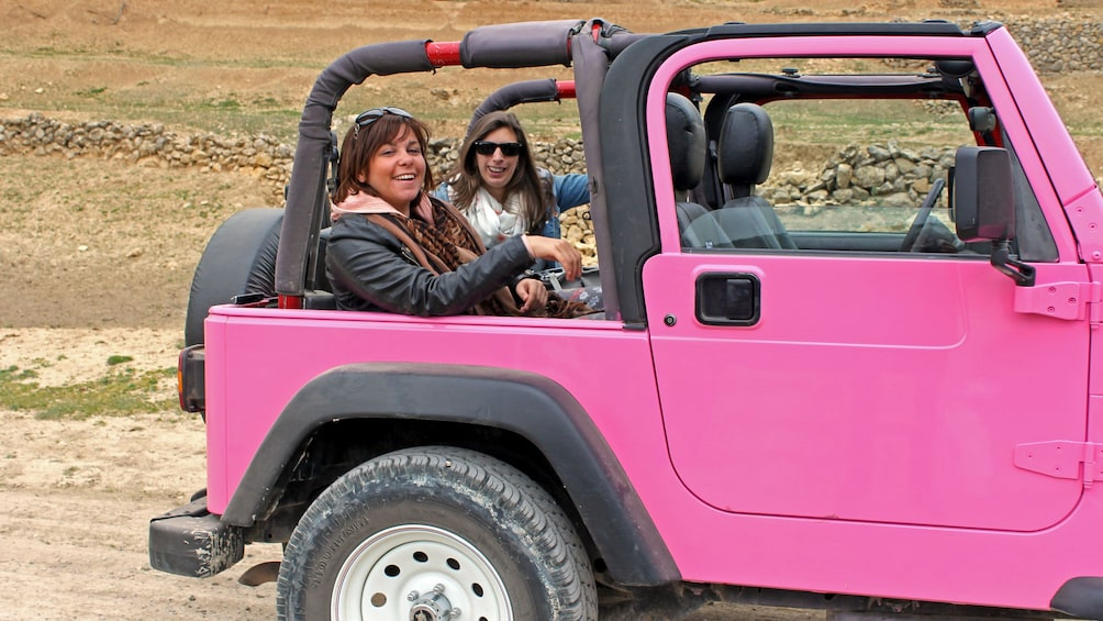 People in the back of a pink Jeep in Costa Blanca