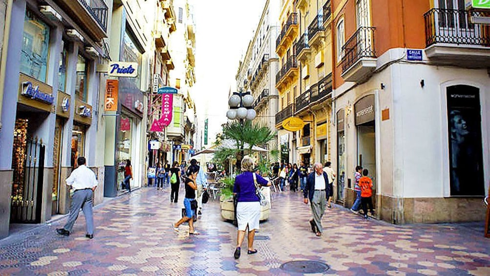 Show item 4 of 5. Storefronts on a bustling street in Valencia