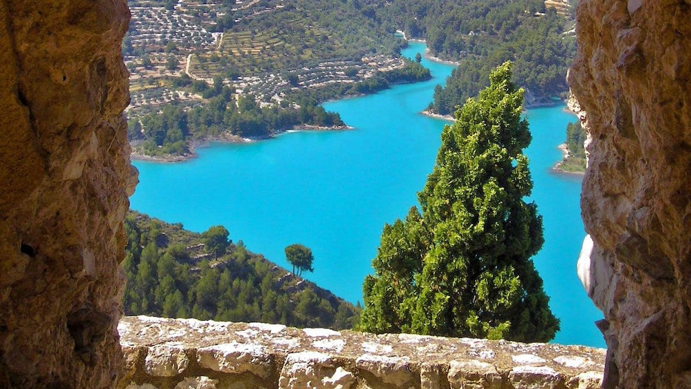 Show item 2 of 5. View of bright cerulean waters from atop a hill in Guadalest