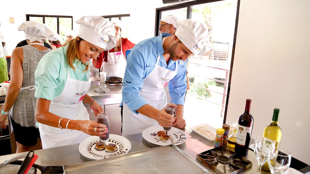 Couple placing chocolate sauce on desserts they made in Cozumel