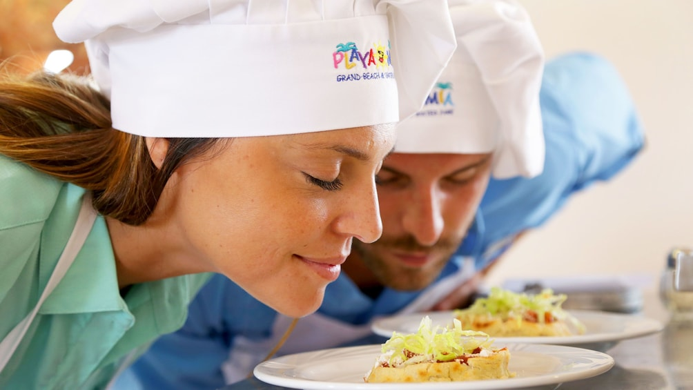 Couple smelling finished cuisine during cooking class in Cozumel