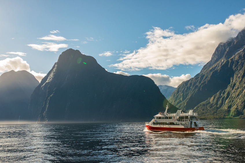 Show item 3 of 10. Landscape view of a boat touring the Milford Sound