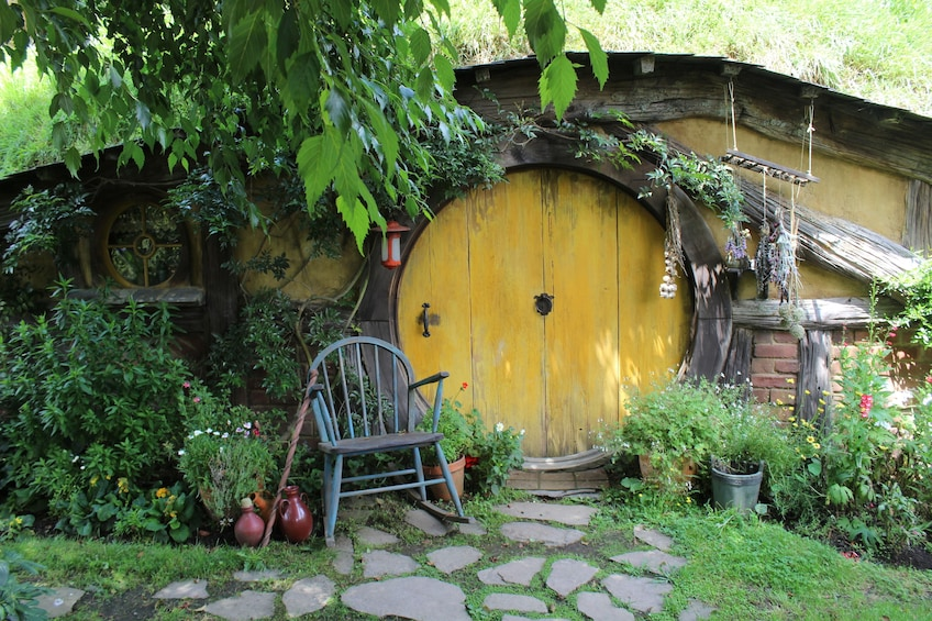 Show item 1 of 4. Large round yellow door of house in Hobbiton in New Zealand