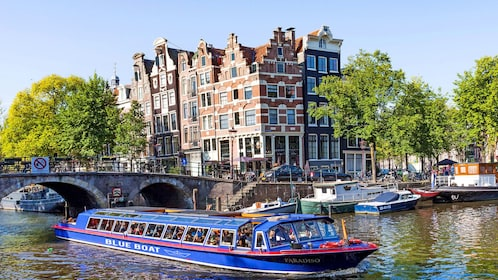 Tour boat in canal posing by historical buildings in Amsterdam