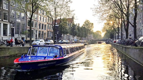 Tour boat traveling through narrow part of canal in Amsterdam