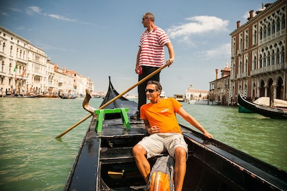 Man and Gondola captain ride through the Grand Canal in Venice