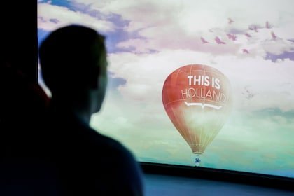 Silhouetted person looking at hot air balloon on a screen