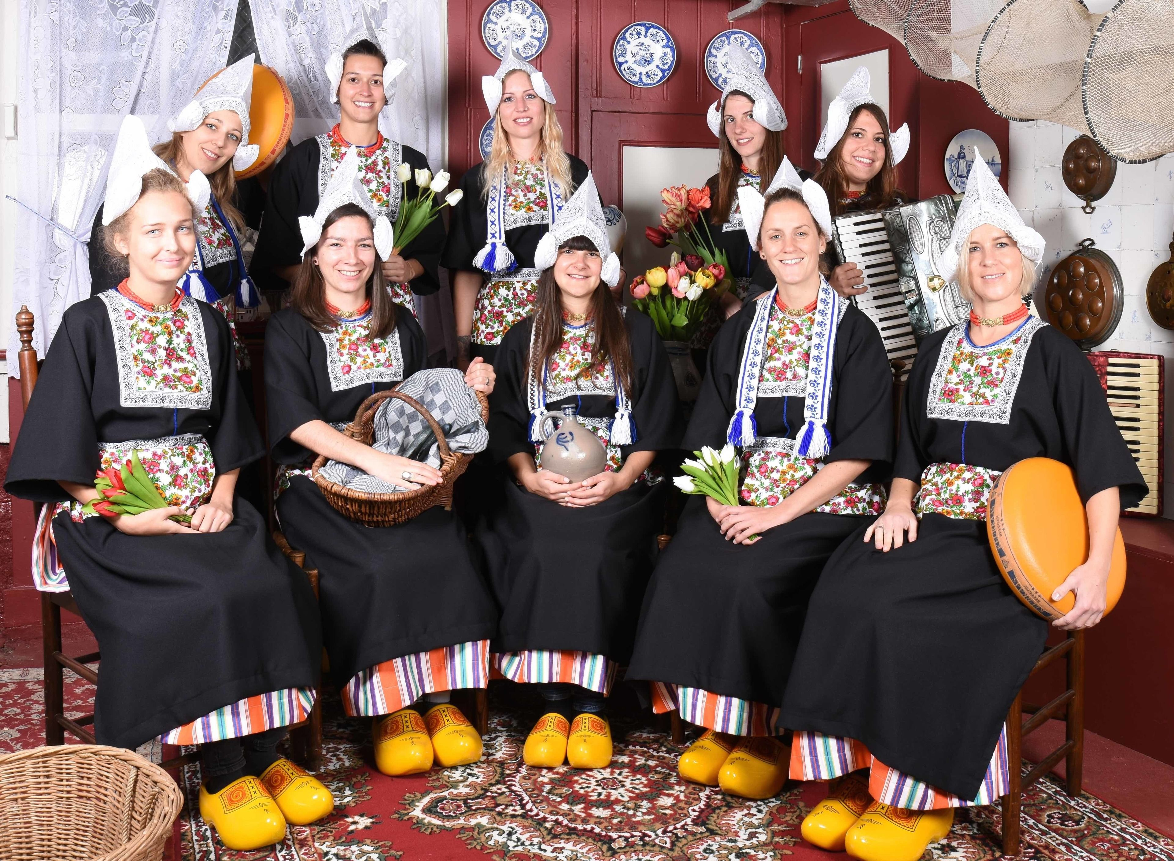 Ten Women in a group dressed in traditional clothing at the Dutch Costume Museum