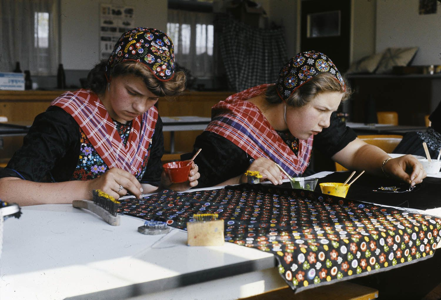 Traditional Dutch women paint fabric at the Dutch Costume Museum workshop